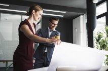 Geschäftsfrau stellt Geschäftsmann am Schreibtisch Plan vor — Stockfoto
