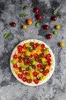 Pizza sin cocer con tomates y hojas de albahaca - foto de stock