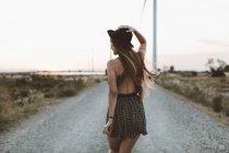 Задній погляд молодої жінки, що ходить по сільській дорозі в вечірній час — стокове фото