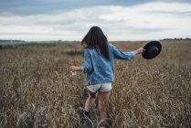 Вид на молодую женщину с напитками и шляпой, гуляющую по кукурузному полю — стоковое фото