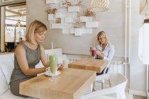 Дві молоді жінки, які користуються смартфонами у кафе. — стокове фото