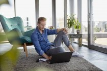 Young man sitting on carpet at home and using laptop — Stock Photo