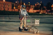 Spaceman in city at night on parking lot with shopping cart — Stock Photo