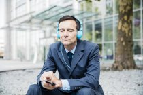 Бизнесмен с закрытыми глазами слушает музыку с наушниками в городе — стоковое фото