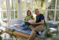 Feliz pareja madura sentada en el sofá en casa con pastel de cumpleaños falso - foto de stock