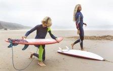 Spagna, Aviles, due giovani surfisti sulla spiaggia che preparano tavole da surf — Foto stock