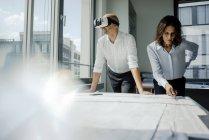 Due architetti che lavorano su cianografie, uomo con occhiali VR — Foto stock
