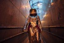 Spaceman en ciudad por la noche que camina en pasillo estrecho - foto de stock