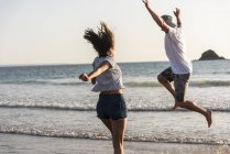 Young couple having fun on beach, running and jumping at sea — Stock Photo