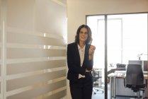 Donna d'affari matura in piedi nel corridoio dell'ufficio e in possesso di mela — Foto stock