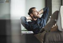 Rilassato uomo d'affari sorridente seduto in ufficio con gli occhi chiusi — Foto stock