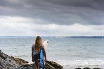 Giovane donna che porta la tavola da surf sulla spiaggia rocciosa in mare — Foto stock