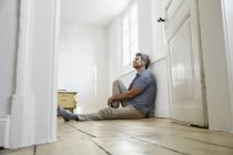 Mature man sitting on floor of bedroom, daydreaming — Stock Photo