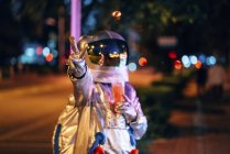 Spaceman in city at night with takeaway drink showing victory gesture — Stock Photo
