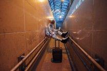Spaceman en la ciudad por la noche con la maleta rodante en el pasillo estrecho - foto de stock