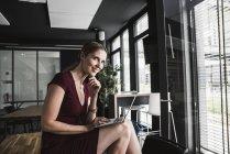 Smiling businesswoman in office wearing burgundy dress using laptop — Stock Photo