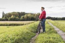 Homem idoso com bicicleta contemplando o caminho na paisagem rural — Fotografia de Stock