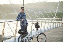 Ritratto di giovane sorridente con bicicletta pieghevole in piedi su un ponte — Foto stock