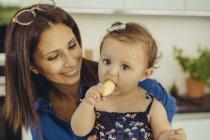 Mère regardant bébé fille manger une pomme — Photo de stock