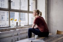 Woman sitting on wooden desk in loft and looking through window — Stock Photo
