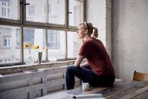 Femme assise sur un bureau en bois dans un loft et regardant par la fenêtre — Photo de stock
