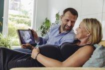 Зрелая беременная пара смотрит 3D-изображение своего нерожденного ребенка на планшетном компьютере — стоковое фото