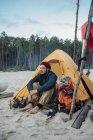 Backpacker homem sentado na frente da tenda na praia de areia — Fotografia de Stock