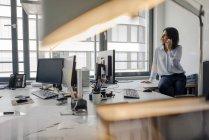 Зрелая деловая женщина, сидящая на столе в офисе, разговаривающая по телефону — стоковое фото