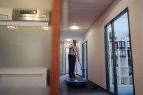 Empresario de pie en paddle board en el pasillo de la oficina - foto de stock