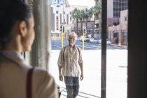 Maduro sorrindo homem olhando para mulher atrás janela vidro painel — Fotografia de Stock