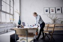 Woman working at desk in design loft — Stock Photo