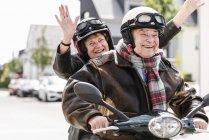 Heureux couple de personnes âgées s'amuser, scooter moteur d'équitation et agitant — Photo de stock