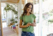 Портрет улыбающейся зрелой женщины, использующей мобильный телефон дома — стоковое фото