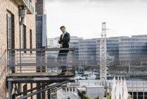 Активный бизнесмен, стоящий на балконе в городе — стоковое фото