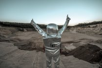 Spaceman raising arms on nameless planet, with thumbs up — Stock Photo