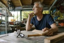 Mature man at workbench in workshop thinking — Stock Photo