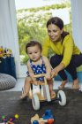 Happy mother with baby daughter driving toy car in living room — Stock Photo