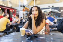 Jovem com telefone celular sentado à mesa e esperando — Fotografia de Stock