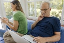 Mature couple sitting on couch at home with man using laptop and woman using cell phone — Stock Photo