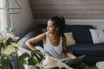 Молодая женщина сидит с ноутбуком на диване, глядя в окно — стоковое фото