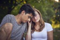 Молодая пара сидит в парке, делится наушниками, слушает музыку — стоковое фото