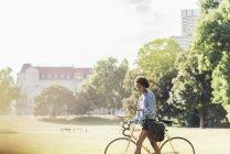 Jovem com telefone celular empurrando bicicleta no parque — Fotografia de Stock