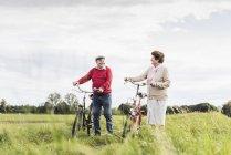 Coppia senior spingendo biciclette nel paesaggio rurale — Foto stock