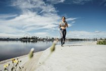Young athletic woman running at riverside — Stock Photo