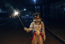 Spaceman standing outdoors at night holding sparkler — Stock Photo