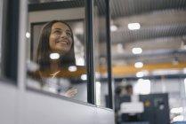 Уверенная женщина, работающая на высокотехнологичном предприятии, выглядывающая из комнаты управления — стоковое фото