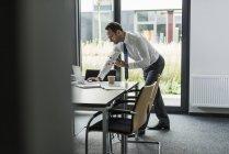 Бізнесмен з атомною моделлю за допомогою ноутбука у своєму офісі. — стокове фото