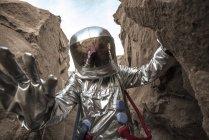 Spaceman exploring nameless planet, examining canyon — Stock Photo