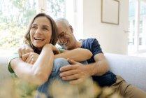 Feliz pareja madura sentada en el sofá en casa - foto de stock