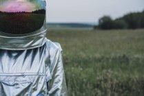 Hombre del espacio de pie en la naturaleza naturaleza, prado que refleja en el sombrero espacial - foto de stock